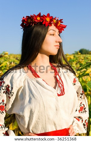 A Ukrainian woman in an authentic 19th century garment looking thoughtful in a ripe sunflower field