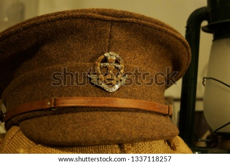 A uniform cap of the British army from World War 1 next to a lantern.