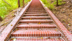 A uniform red brick staircase going up the mountain