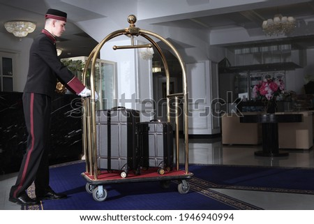 A uniformed doorman pushes a luggage cart .Several leather suitcases stand on a luggage cart. Hotel service.The holiday season. Free space. Сток-фото ©