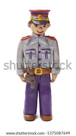 A uniformed policeman with a holster made of plasticine. Children and the profession