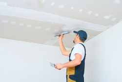 A uniformed worker applies putty to the drywall ceiling. Putty of joints of drywall sheets.