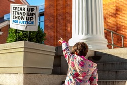 A unique abstract image where a little girl is pointing a sign post that says speak up, stand up, show up for justice. A concept image for social awareness, equality, human rights, non discrimination.