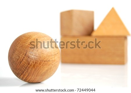 A Unique Set of Wooden Blocks, With a Wooden Sphere in the Foreground and Wooden Blocks Stacked Together in the Background, On White