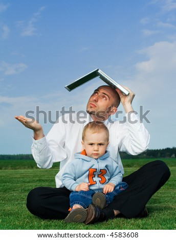 A unique view of a man with his small son in his lap, sitting out in an open field, holding a laptop computer over his head and extending his hand as if to check for rain.