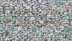 A unique wall that contains white pebbles that are held up by iron ram
