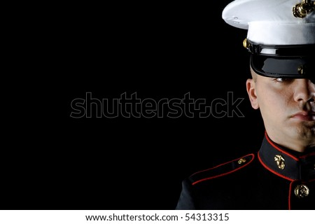 A United States Marine wearing Dress Blues in a studio environment