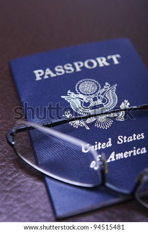 A United States of America Passport with a pair of glasses