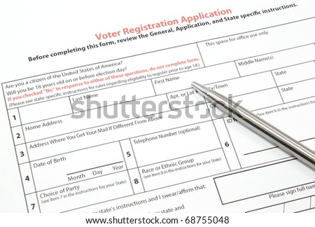 A United States voter registration application ready to be filled out with a silver pen.