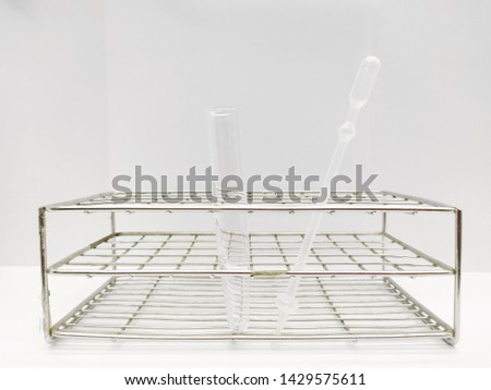 A urine centrifuge tube and disposable graduated plastic pipette in stainless wire tube rack on white background. #1429575611