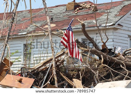 A US American flag rises above a home ruined by a deadly EF-5 tornado.