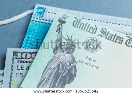 A US stimulus check on with some one-hundred-dollar bills and a medical mask