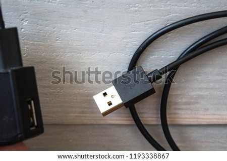 a usb cord with charger on wooden background #1193338867