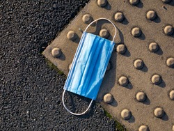 A used, blue surgical mask used for COVID-19 PPE protection, discarded as litter on a pavement / sidewalk in an urban area causing environmental pollution