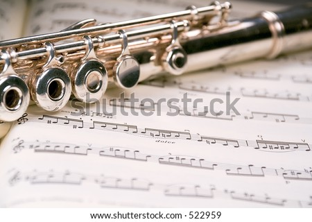 A used flute rests across an open musical score. Only one line of music is in focus.