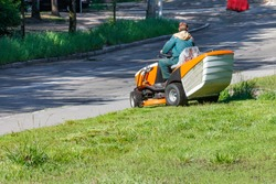 A utility worker using a professional lawn mower mows tall grass along the side of a city road on a clear sunny day, copy space.