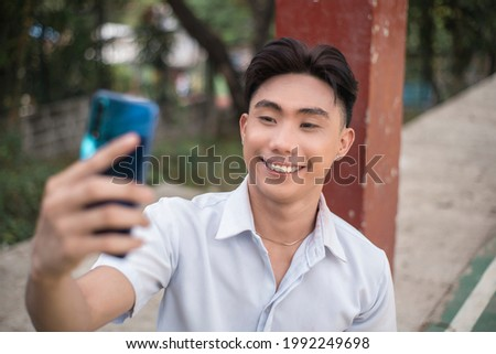 A vain handsome young man takes a selfie of himself while at a basketball court. A Narcissistic asian guy. Stock photo ©