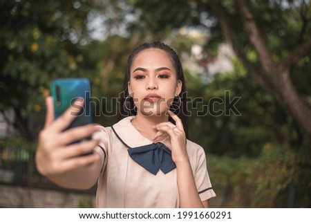 A vain young asian woman in a student uniform takes a selfie of herself while outdoors. Taking a photo for social media trying to get likes. Stock photo ©