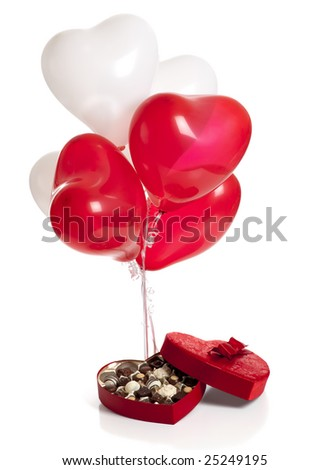 A Valentines day background consisting of chocolates in a heart shaped box and heart shaped balloons on a white background