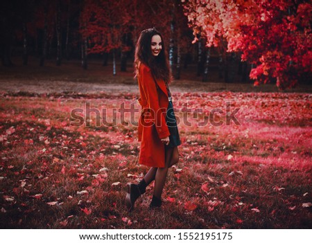 A vampire. Red trench coat. Mysterious stranger. Girl with a wonderful smile. Mystical atmosphere. Paranormal another world. Background wallpaper. Fairytale forest. Autumn atmosphere. Dreamy park.
