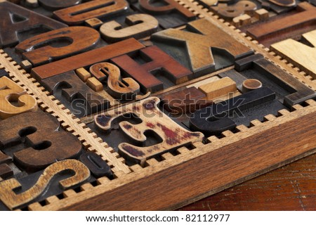a variety of antique wood letterpress printing blocks in vintage typesetter box