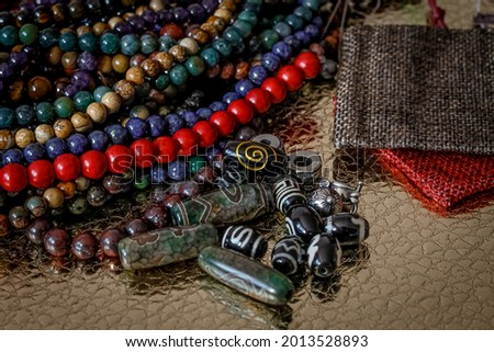 a variety of beads made of natural stones, Tibetan ji beads and metal inserts are randomly scattered on the golden surface next to beautiful red and beige linen bags