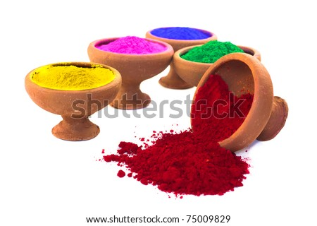 A variety of colored dyes in earthen bowls isolated on white. The red color is spilled.
