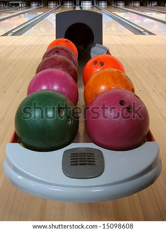 A variety of colorful bowling balls sitting in the ball return at the bowling alley.