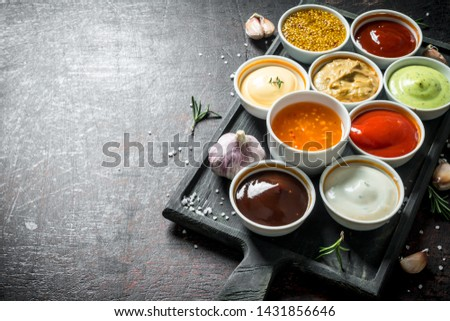 A variety of delicious sauces with slices of garlic. On dark rustic background Stockfoto ©