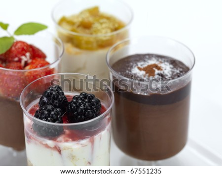 a variety of desserts,a chocolate mousse with strawberries,a cheese cake with raspberries,a double chocolate mousse and a cheese cake with peach
