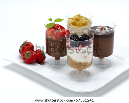a variety of desserts,a chocolate mousse with strawberries,a cheese cake with raspberries,a double chocolate mousse and a cheese cake with caramel peach