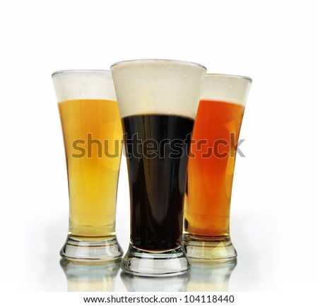 A variety of different color beer in glass cups on a white background. Foam is on the alcohol glasses. There is a isolated, white background.