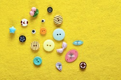 A variety of different sewing buttons over a yellow fuzzy background.