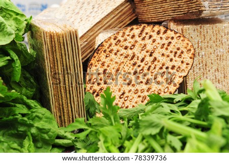 A variety of different types of matza (unleavened bread) surrounded by green vegetables such as lettuce and celery - traditional food used on the Jewish religious holiday feast of Passover (pesach).