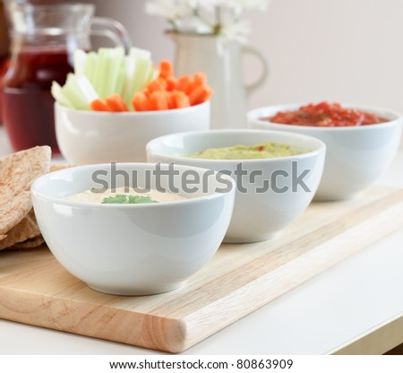 A variety of dips, with pitta bread, crudites and juice on a table.
