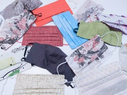 A variety of fabric face masks scattered on a white table