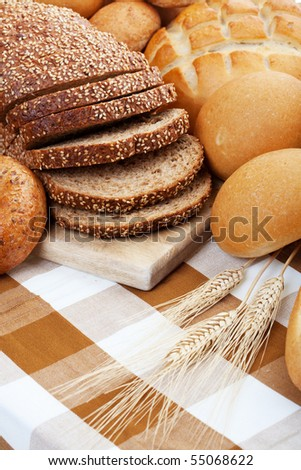 A variety of freshly baked breads along with three stocks of wheat.  Shallow depth of field.