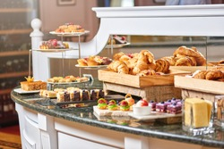 A variety of freshly made pastry in the sunlight, luxury hotel breakfast buffet isolated, restaurant interior