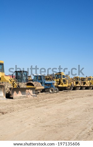 A variety of heavy duty machinery lined up together in a yard.