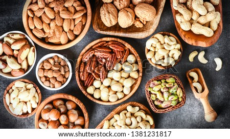 A variety of nuts in wooden bowls from top view. Walnuts, cashew, almond, pistachio, pecan, hazelnut, macadamia nut selection. Healthy super food.