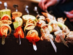 A variety of skewered meats and vegetables cooking on the grill