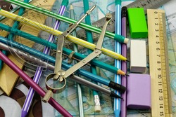 A variety of stationery in a chaotic mess are spread out on the table, background