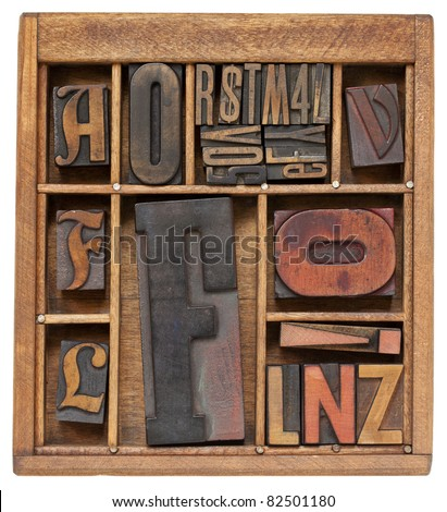 a variety of vintage letterpress printing blocks with big letter F in a small wooden typesetter box with dividers, isolated on white