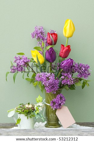 A vase of bright colored tulips and lilac in a vase with a blank gift tag and spring decorations, vertical