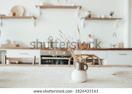 A vase with dry flowers on a table. Scandinavian classic kitchen with wooden and white details, minimalistic interior design. Real photo.Cosy home.