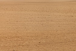 A vast brown ploughed cultivated soil, land texture background
