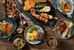 A vegetarian barbecue grill and various gourmet dishes on a rustic timber table.