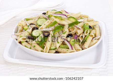A vegetarian pasta salad with a basil pesto dressing, olives, red onion, cucumber and green pepper, sprinkled with parsley.