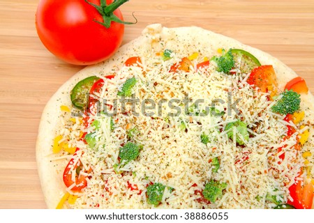 A veggie pizza ready to go into the oven topped with sharp cheddar and asiago cheese, fresh tomatoes, red bell pepper, mild jalapeno chilie, broccoli and dried herbs