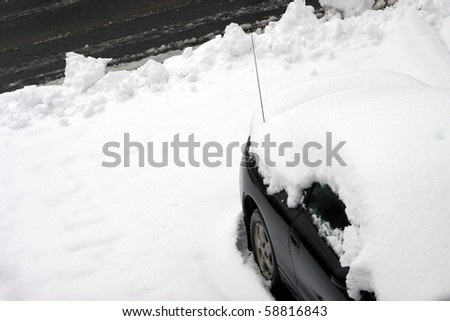 A vehicle covered in snow and snowed in just after the city plow passed the driveway.